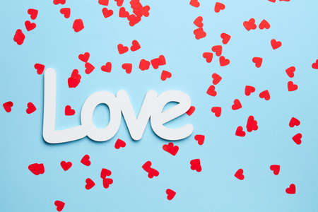 Texture of red little hearts spilled on blue background with love