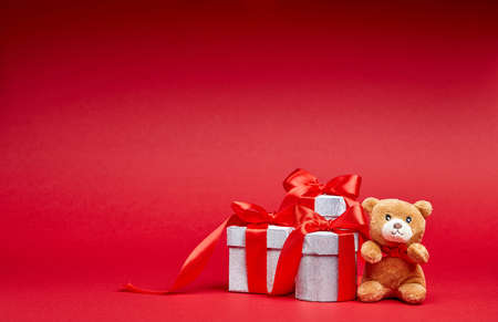 joyeux: Christmas gifts on red background with toy and ribbons