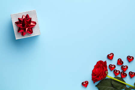 Plain blue background with red rose, silver gift and little hearts