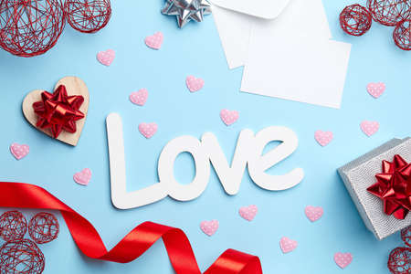 Blue plain background with silver gift, red ribbon, white love letter and sign