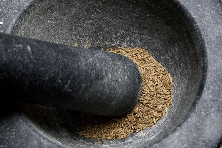 enhancer: pestle and mortar with herbs and spices, coriander