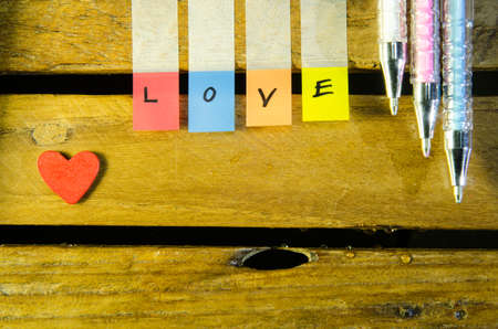 Love alphabet and little red heart and color pen on wood pattern background photo
