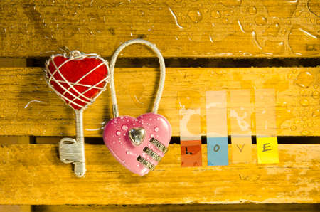 master key: Pink master key with red heart keyand love alphabet on wood pattern background Stock Photo