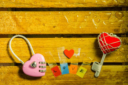 master key: Pink master key with red heart key and love alphabet on wood pattern background Stock Photo