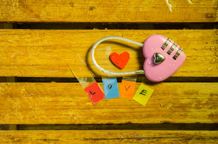 master key: Pink master key and love alphabet on wood pattern background Stock Photo