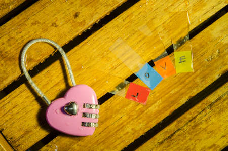 Pink master key and love alphabet on wood pattern background photo