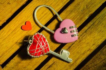 master key: Pink master key and red heart key on wood pattern background Stock Photo