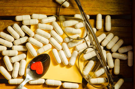 pharmaceutical company: Capsule drug with glasses and little red heart on wood pattern background