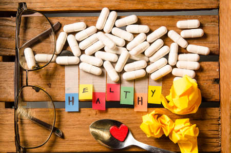 pharmaceutical company: Healthy alphabet and capsule drug with glasses on wood pattern background Stock Photo
