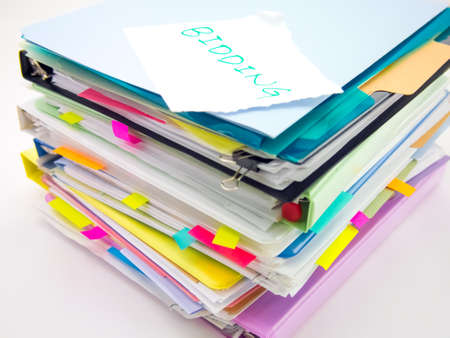 bidding: There is the huge pile of business documents on the desk.