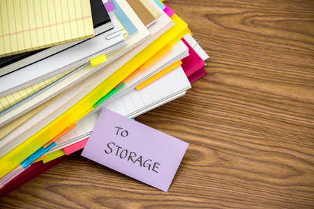 stack of documents: To Storage; The Pile of Business Documents on the Desk Stock Photo