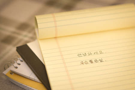 bilingual: Korean; Learning New Language Writing Greetings on the Notebook (Translation; Good Morning) Stock Photo