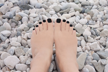 pedicure with black nails on the pebbles beach