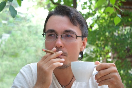 gigolo: Young handsome man smoking cigar and drinking coffee Stock Photo