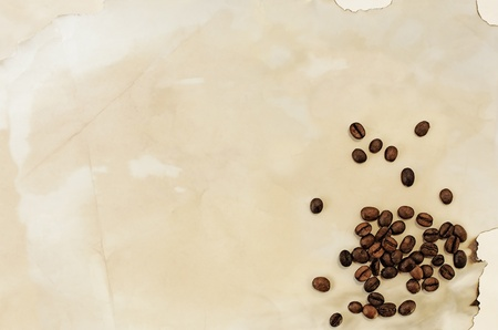 textured coffee beans on an handmade old paper, vintage background photo