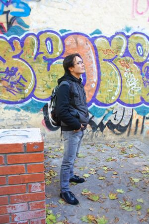 adult handsome man posing outdoors in a graffiti wall background photo