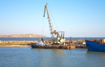 small ship and crane in sea port photo