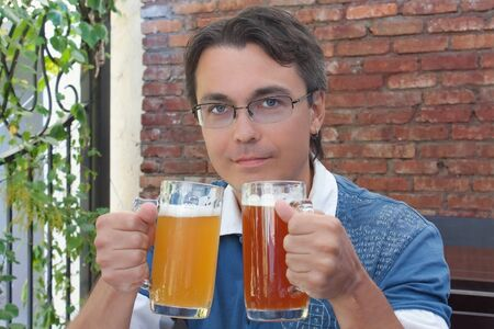 Portrait of smiling young man holding two glasses with beer in pub photo