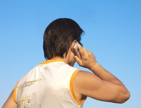 hands behind head: man talking on a mobile phone against blue sky. Back view.