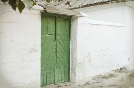 Green Wooden vintage door to the whitewashed building photo