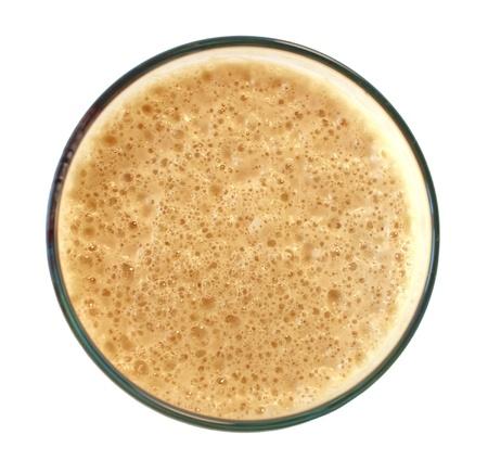 stout: vaso de cerveza con espuma de cerveza negra oscura sobre fondo blanco, vista desde arriba
