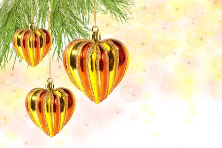 Red and gold hearts- christmas balls on pine tree branch on beautiful Christmas background photo