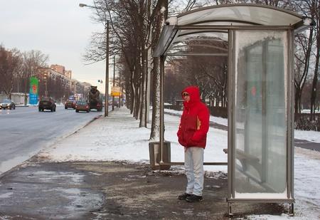 fermata bus: L'uomo in piedi in una pensilina in attesa di un bus Archivio Fotografico