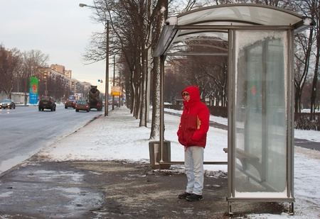 bus stop: Man standing in a bus shelter waiting for a bus