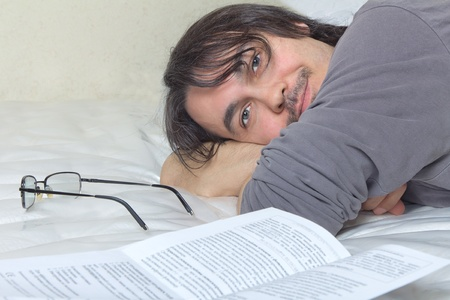 Handsome Caucasian middle aged adult man lying in bed and reading photo
