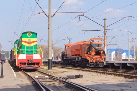Railway heavy duty machines train and Freight multicolored diesel train on the station, Bucha, Ukraine photo
