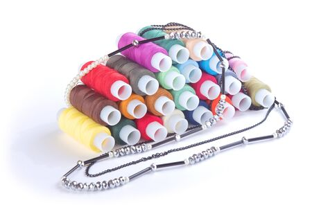 Colorful threads and beads on white background photo