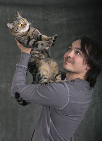 handsome man hold his lovely tabby british cat photo