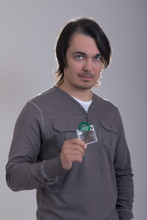Handsome man holding green condom, on gray background Stock Photo - 13376025