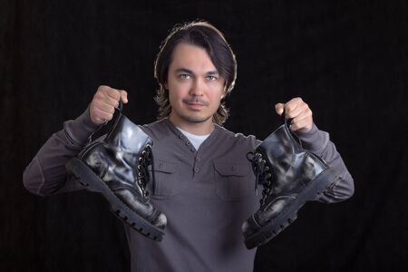 Young man holding old black boots in his hands, on black background photo
