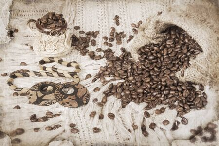 ceramic cup of coffee, roasted coffee beans and wooden bijouterie on canvas background in vintage style photo