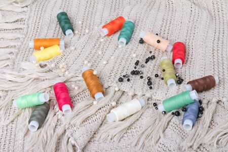 Close up of colorful threads and beads on a fabric background photo