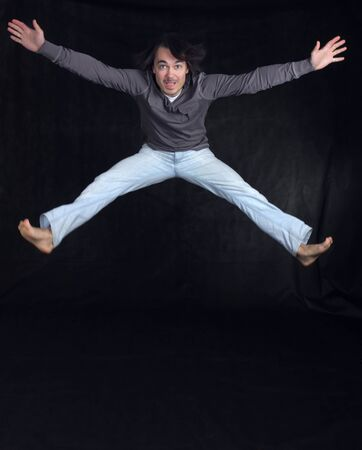 Young handsome man jumping, over black background photo