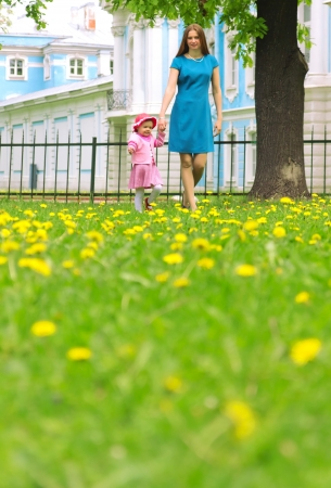 Mother and child walking in green grass photo