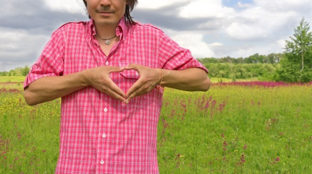 Male hands making an heart shape on a nature background. ecology concept photo