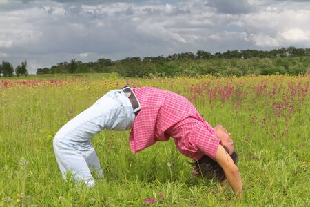 Young man in wheel pose in summer meadow Stock Photo - 14014649