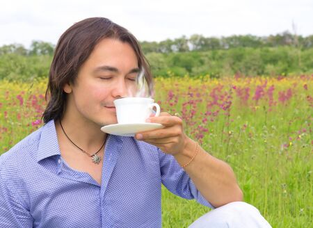 Portrait of young happy smiling man drinking coffee or tea outdoors Stock Photo - 14014679