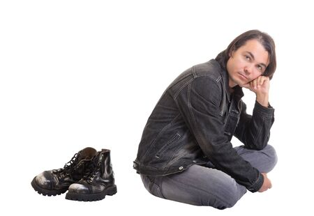 Young casual man sitting on the floor while barefoot, isolated on white background Stock Photo - 14037996