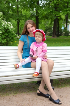 A young mother sitting on a park bench with her daughter in her arms photo