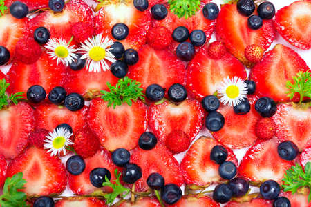 fresh cut strawberries, blueberries and camomile flowers textural background photo