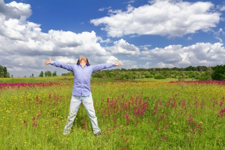 Young man standing on a meadow with raised hands and looking to a sky Stock Photo - 14157868