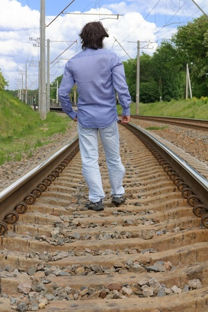 Young man walking on the railway tracks photo