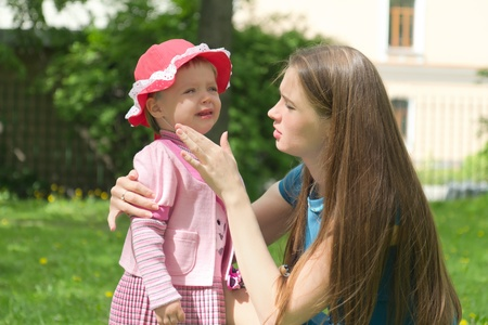 Little girl crying in mothers arm in summer park photo
