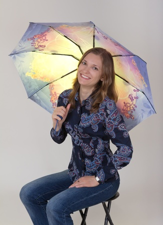 Young beautiful woman holding umbrella, on grey background photo