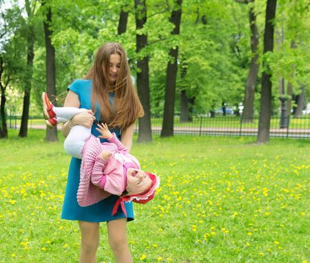 Young mother holding daughter head over heels in spring park photo