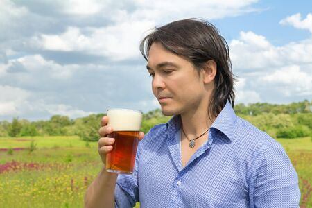 Young man holding a glass of beer outdoors Stock Photo - 14426175